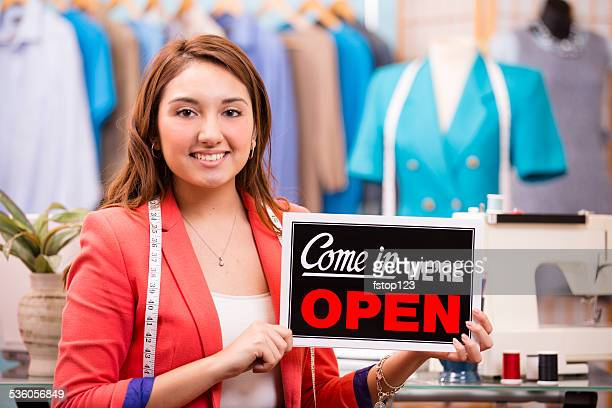 latin woman small business owner. fashion designer, boutique. open sign. - mexican business women stock photos and pictures