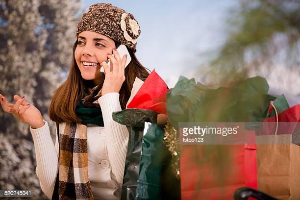 Mujer Latina conversaciones por teléfono celular.  Navidad bolsas de compras al aire libre.
