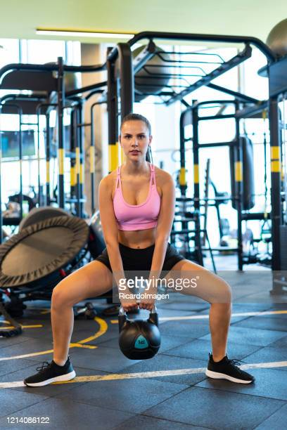 latin woman using dumbbell in the gym - musculoso stock pictures, royalty-free photos & images