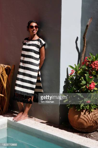 latin woman wearing a black and white handwoven dress and sunglasses standing by pool, smiling - fringe dress stock pictures, royalty-free photos & images