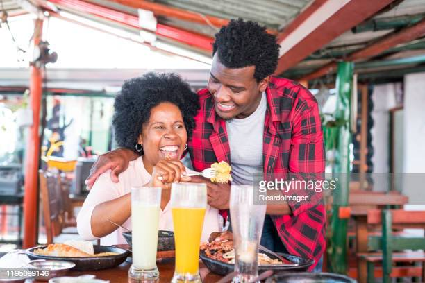 latin woman with dark skin and afro hair of approximately 50 years dressed casually is sitting at a restaurant table where she has lunch with her family typical colombian food while her son-in-law latin man with brown skin and afro hair looks at her - 55 59 years stock pictures, royalty-free photos & images