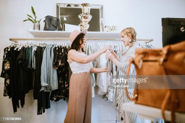 latina boutique store eigenaar assisteren klant - dameskleding stockfoto's en -beelden