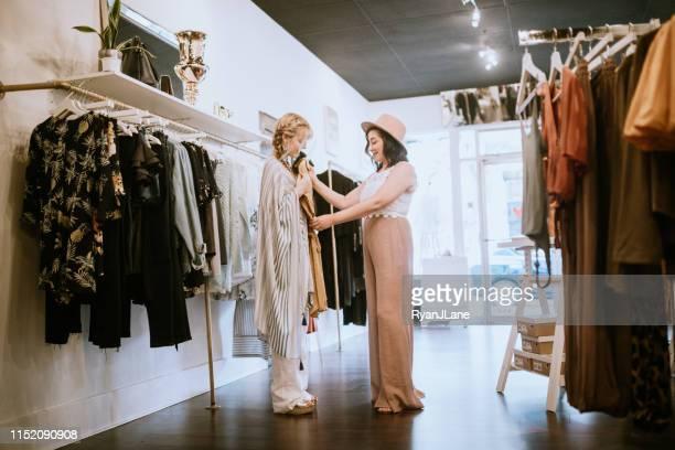 latina boutique store eigenaar assisteren klant - the past stockfoto's en -beelden