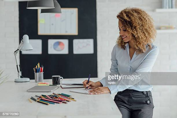 latina businesswoman coloring book in her office. - colouring book stock photos and pictures