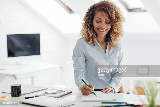 latina businesswoman coloring book in her office. - colouring book stock pictures, royalty-free photos & images