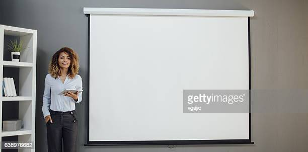 latina businesswoman having presentation in her office. - projection screen stock pictures, royalty-free photos & images