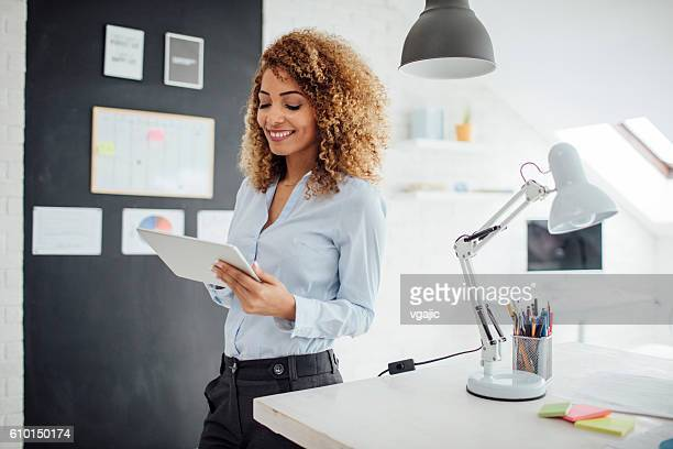 Latina Businesswoman Using Digital Tablet In Her Office