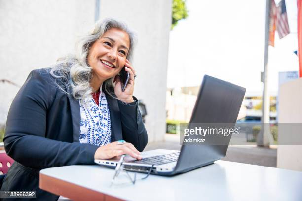latina businesswoman using laptop at cafe - sales occupation stock pictures, royalty-free photos & images
