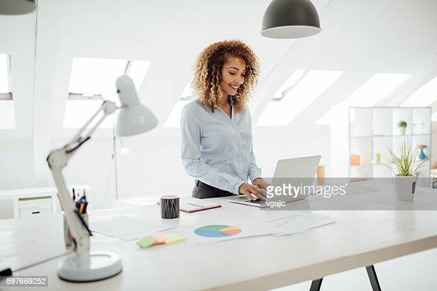 latina businesswoman working in her office. - staan stockfoto's en -beelden