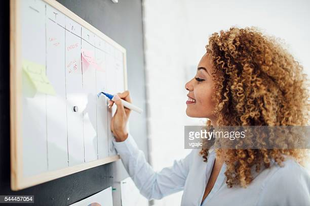 latina businesswoman writing schedule. - personal organiser stock photos and pictures