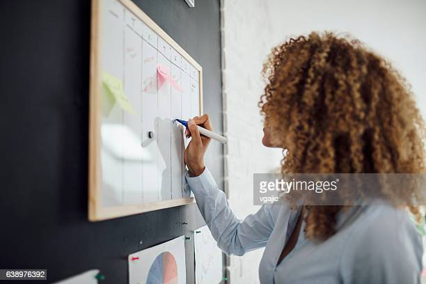 latina businesswoman writing schedule. - personal organiser stock pictures, royalty-free photos & images