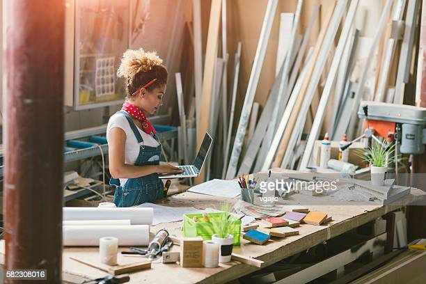 latina carpenter standing in her workshop - business owner stock photos and pictures