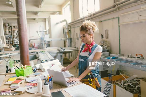 Latina Carpenter steht im Ihren Werkstatt