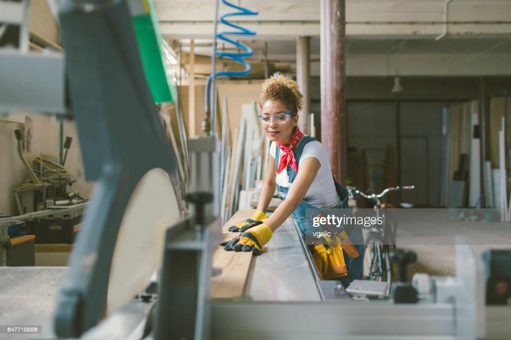 Latina Carpenter working on circular saw : Stock Photo
