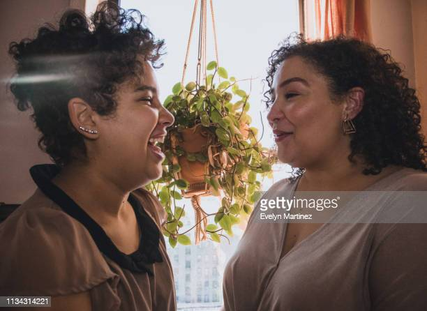 Latina daughter laughing and Latina mother smiling. A house plant and curtain are in the background.