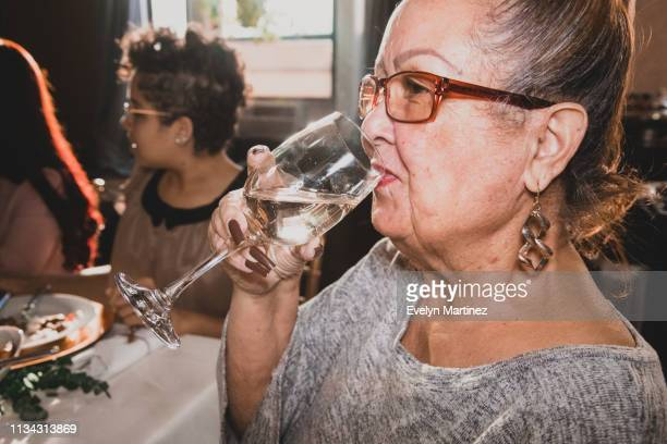 Latina grandmother drinking prosecco out of glass. Dinner party in the background. Partial view on the right side of the kitchen.