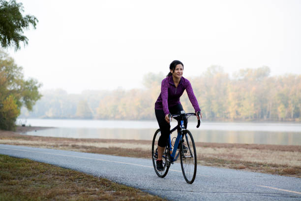 Latina Hispanic woman athlete riding a bicycle in park near lake