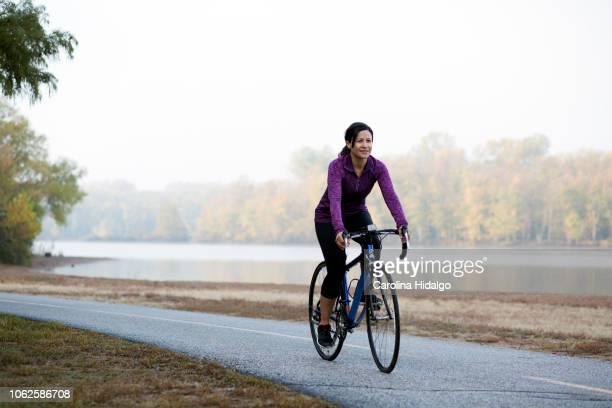 Latina Hispanic woman athlete riding a bicycle in park near lake