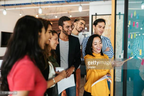 latina leadership in business - group of mexican, cuban and international coworkers in brainstorming session - initiative stock pictures, royalty-free photos & images