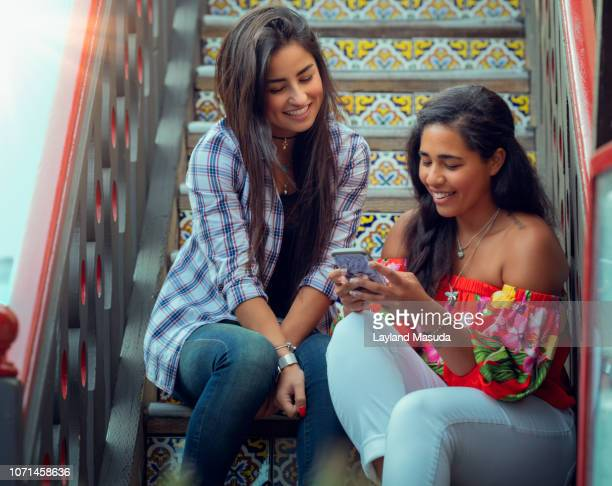 latina millennial girlfriends sharing photos on stairway - redondo beach california stock pictures, royalty-free photos & images