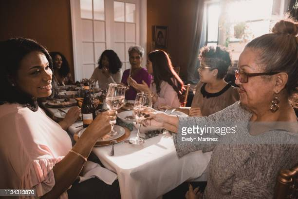 latina mom and latina grandmother smiling and holding out glasses for a celebratory toast. background is a dinner party in the apartment - evelyn martinez stock pictures, royalty-free photos & images