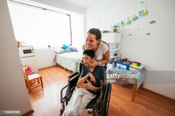 latina mother massaging her son with celebral palsy - wheelchair stock pictures, royalty-free photos & images