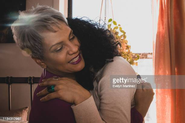 Latina mother with gray hair embracing her daughter with black hair. House plant, curtains and bed in the background.