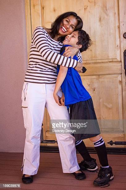 Latina soccer mom mother gives son a big hug