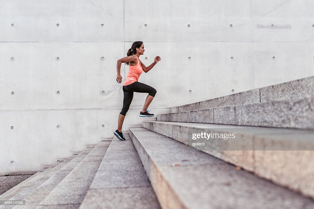 latina sports woman running up outdoor stairway in berlin : Stock Photo