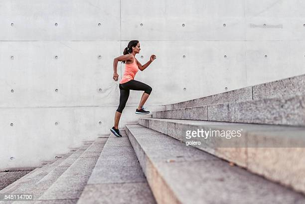 latina sports woman running up outdoor stairway in berlin - stairs stock photos and pictures