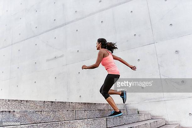 latina sports woman running up outdoor stairway
