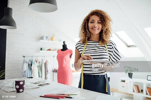 latina tailor using digital tablet in her workshop - tailor - fotografias e filmes do acervo
