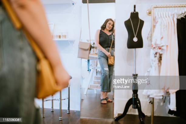 latina vrouw proberen op kleding in boutique store - the past stockfoto's en -beelden