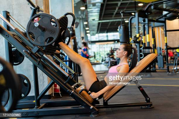 latina woman using leg press in the gym - musculoso stock pictures, royalty-free photos & images