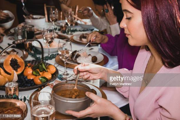 Latina woman with red hair is serving beans onto her dinner plate. Background is a dinner party.