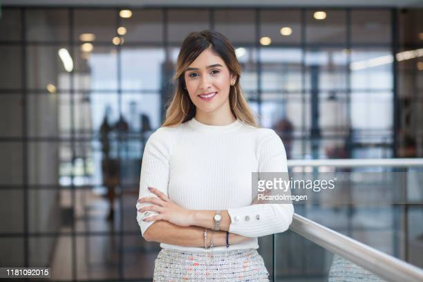 latin-haired latina woman with her arms crossed looking at the camera while smiling - funcionário imagens e fotografias de stock
