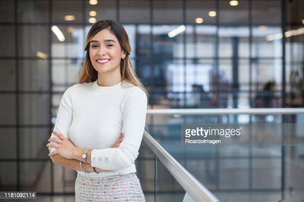 latin-haired latina woman with her arms crossed looking at the camera while smiling - waist up stock pictures, royalty-free photos & images