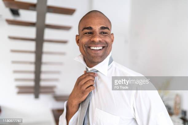 latino afro man getting dressed at home portrait - adjusting necktie stock pictures, royalty-free photos & images