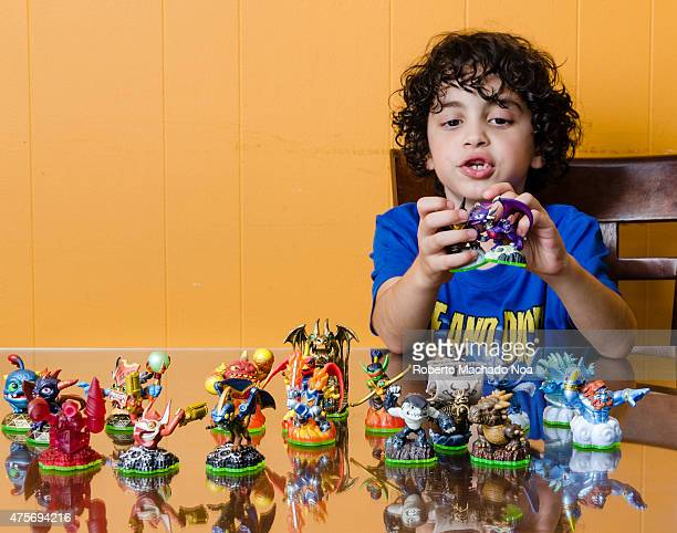 Latino boy playing with action figure toys on reflective table top