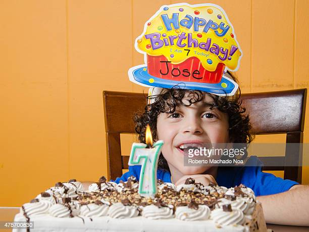Latino boy with cake celebrating his seventh birthday seated on a wooden chair and wearing a birthday cap