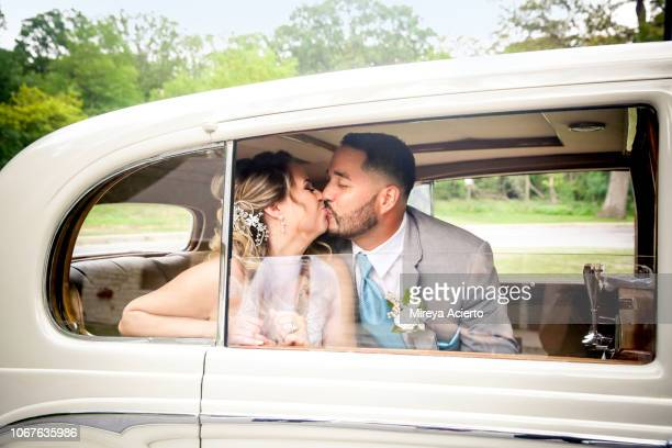 A latino bride and groom seen kissing through the window in a white car on their wedding day.