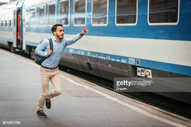 latino businessman is late for the train - beat the clock stock photos and pictures