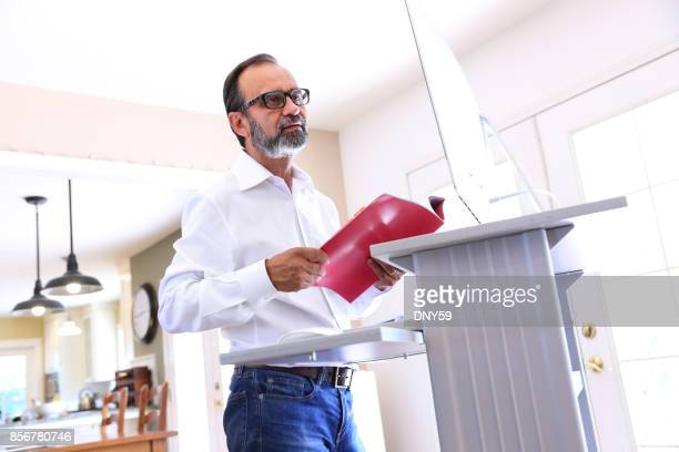 latino businessman works at standing computer desk at home - ergonomics stock photos and pictures