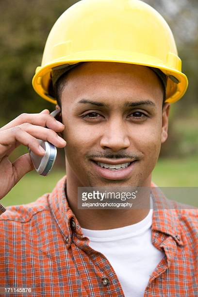 latino construction worker smiling on cell phone