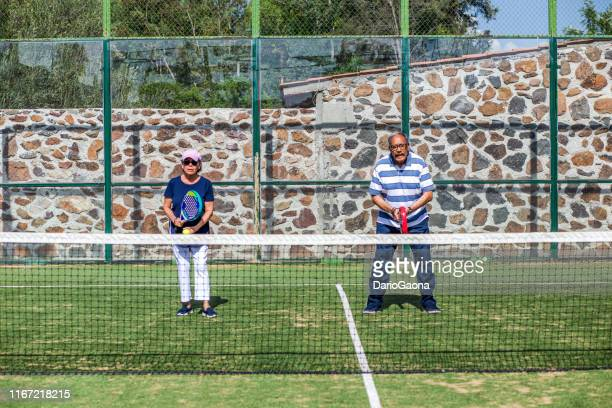 latino couple of retirees playing padel - racket sport stock pictures, royalty-free photos & images