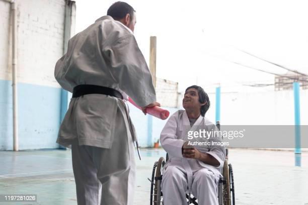 homem novo incapacitado latino que olha com alegre em seu professor do parakarate e que sorri - artes marciais - fotografias e filmes do acervo