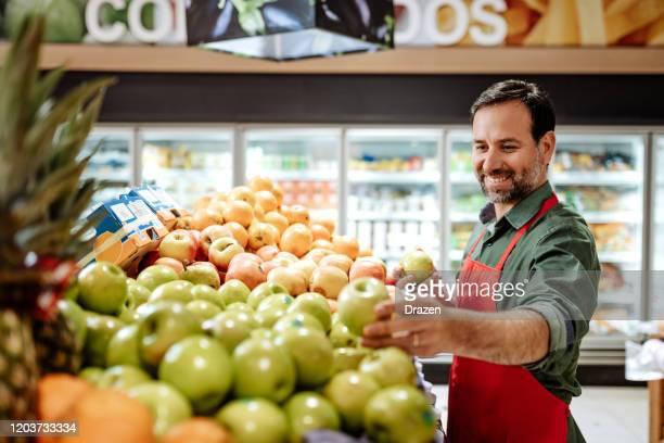 latino-mitarbeiter im supermarkt arrangieren obststapel - employee stock-fotos und bilder