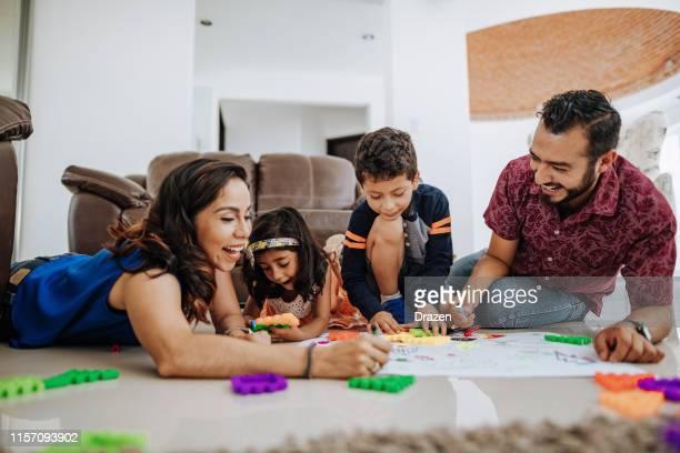 ラテン系の家族は、家で一緒にいて、子供たちと遊んで楽しんでいます。 - メキシコ人 ストックフォトと画像