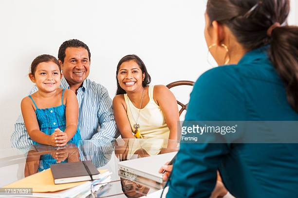 Latino family in a meeting with a female business woman.