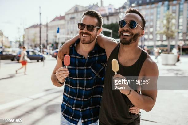 couples gais latinos voyageant en été et mangeant la glace - beautiful gay men photos et images de collection
